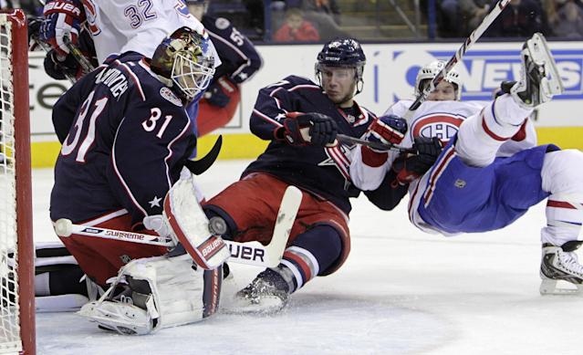 Columbus Blue Jackets' Curtis McElhinney, left, makes a save as teammate Ryan Murray, center knocks Montreal Canadiens' David Desharnais to the ice during the first period of an NHL hockey game Friday, Nov. 15, 2013, in Columbus, Ohio. (AP Photo/Jay LaPrete)