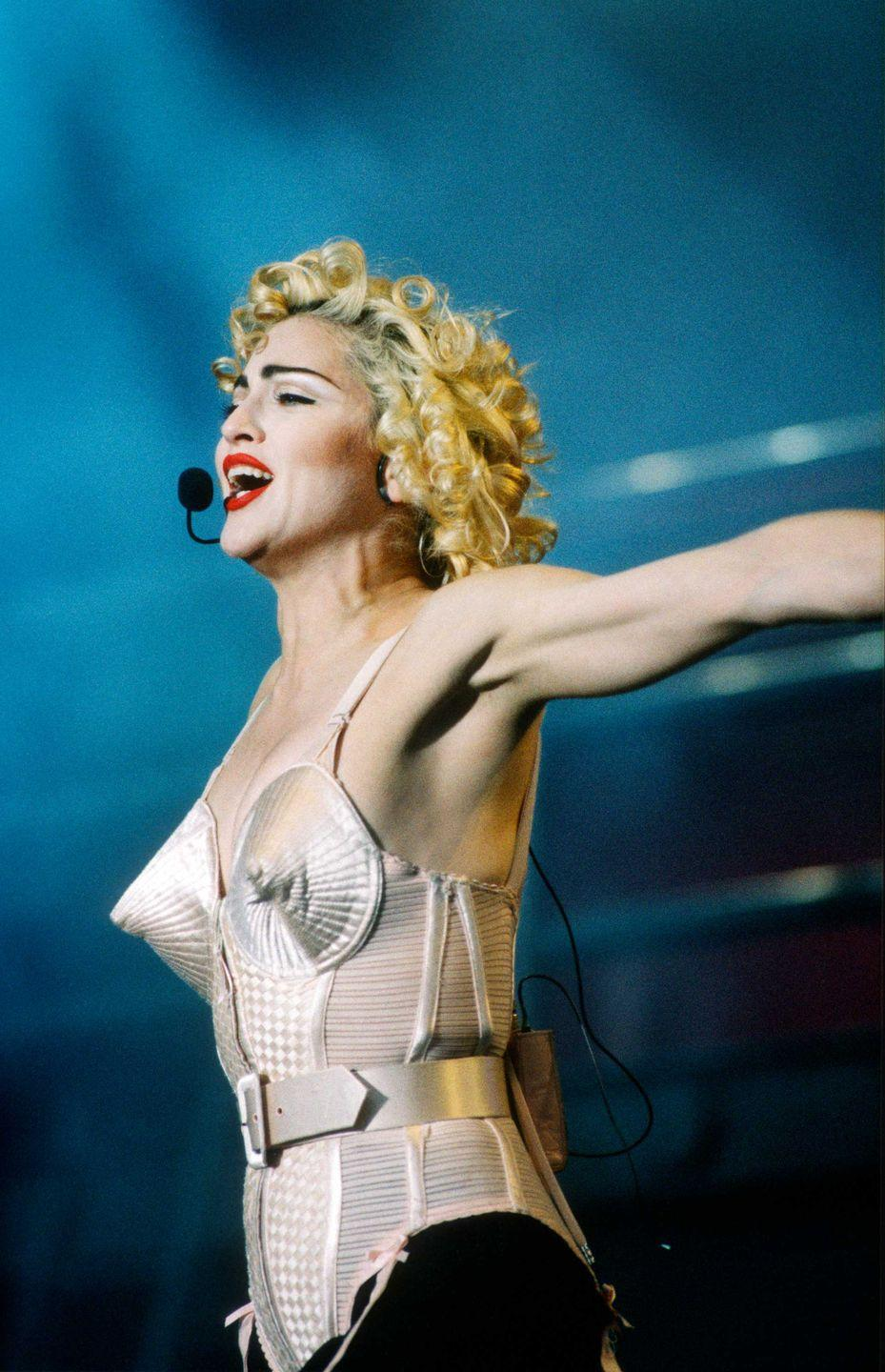<p>Wearing a Jean Paul Gaultier conical bra corset, the Queen of Pop Madonna sings her heart out on her Blonde Ambition Tour in 1990. </p>