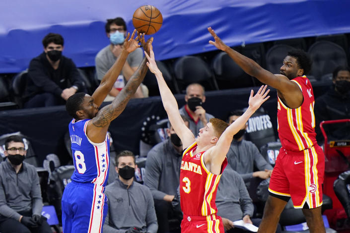 Philadelphia 76ers' Shake Milton, left, goes up for a shot against Atlanta Hawks' Kevin Huerter, center, and Solomon Hill during the second half of Game 2 in a second-round NBA basketball playoff series, Tuesday, June 8, 2021, in Philadelphia. (AP Photo/Matt Slocum)