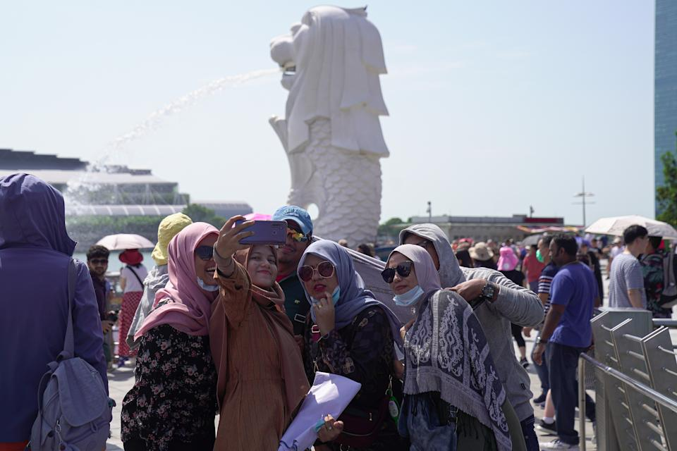 SINGAPORE, SINGAPORE - JANUARY 26: Visitors wearing masks take a selfie on a phone at the Merlion Park on January 26, 2020 in Singapore. Singapore has confirmed four cases of the deadly coronavirus, which emerged last month in the city of Wuhan in China. (Photo by Ore Huiying/Getty Images)