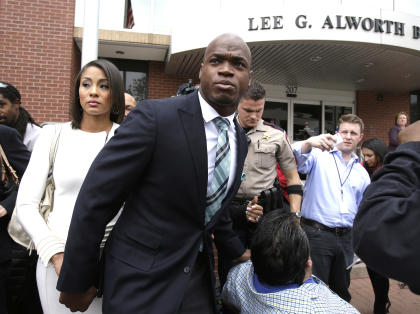 Adrian Peterson leaves the courthouse with his wife Ashley Brown Peterson on Nov. 4, 2014. (AP)