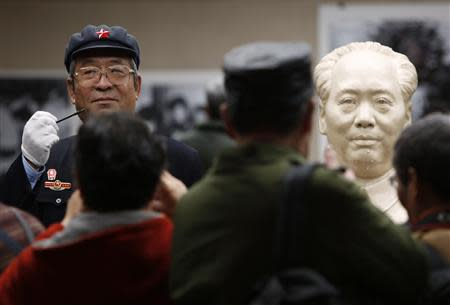 People look on as a man in a Red Army hat stands next to a statue of China's late Chairman Mao Zedong at an exhibition held to commemorate Mao's 120th birth anniversary in Shanghai
