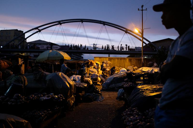 Traders walk across a footbridge in Adum market at nightfall in Kumasi, Ghana. (Photo: Francis Kokoroko/Reuters)