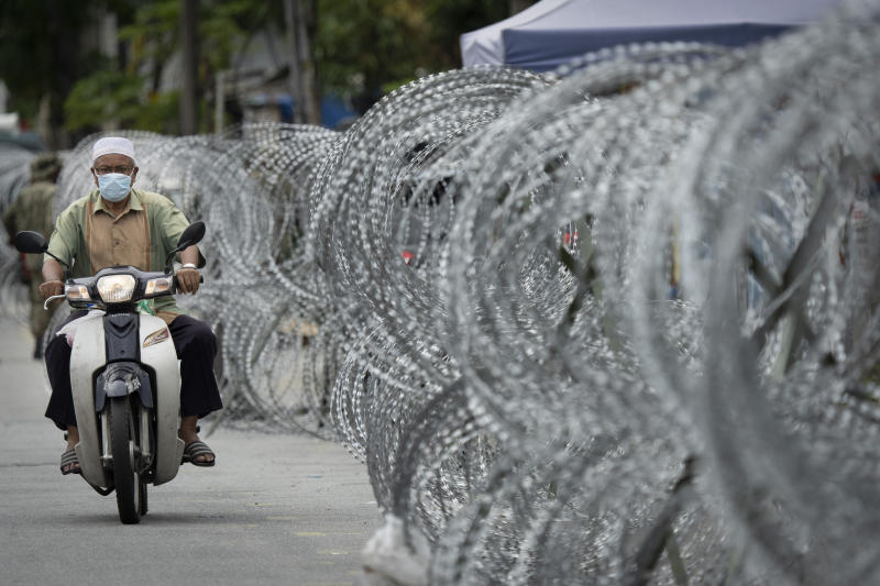 A motorcyclist rides along a barbed wire fence in the virus lockdown area of Selayang Baru, outside Kuala Lumpur, Malaysia, on Sunday, April 26, 2020. The lockdown was implemented to allow authorities to carry out screenings to help curb the spread of coronavirus. (AP Photo/Vincent Thian)