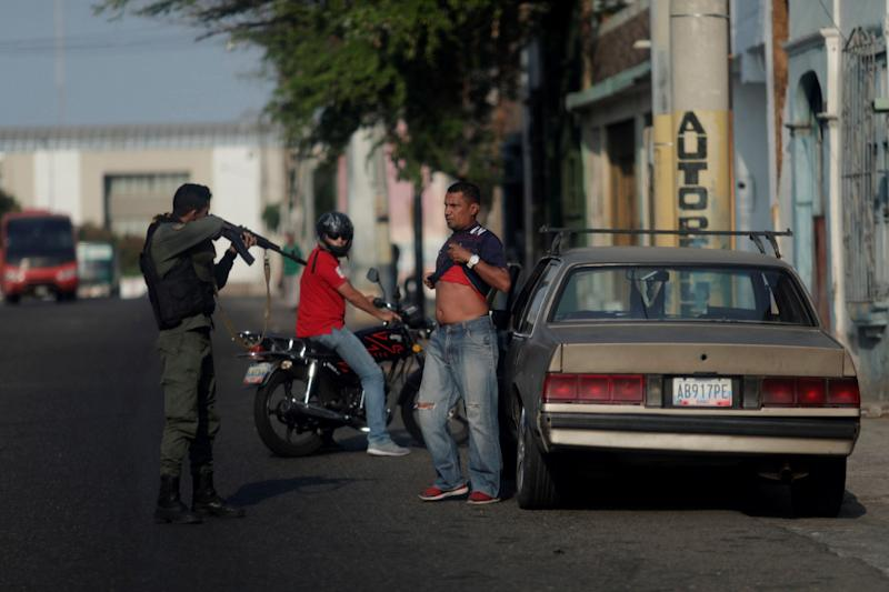A Venezuelan police officer orders a man to lift his shirt during a blackout in Maracaibo, Venezuela. (Photo: Ueslei Marcelino/Reuters)