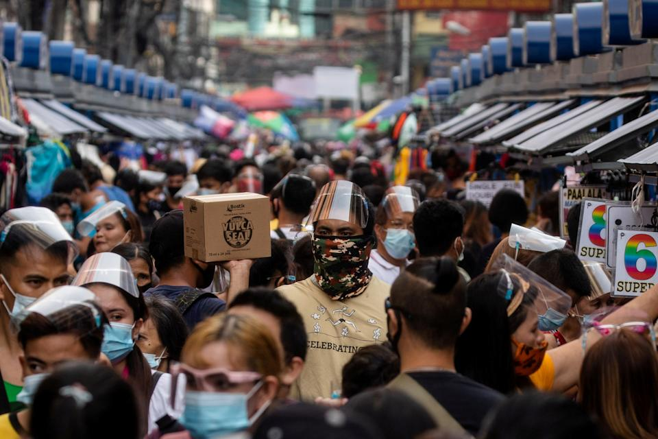 FILE PHOTO: Filipinos wearing masks and face shields for protection against the coronavirus disease (COVID-19) walk along a street market in Manila, December 3, 2020. (Sources: REUTERS/Eloisa Lopez)
