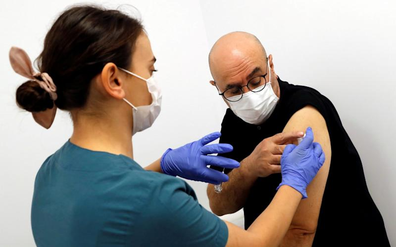 A health worker injects an experimental Chinese coronavirus disease (COVID-19) vaccine to volunteer and doctor Naim Celik as Turkey began final Phase III trials at Kocaeli University Research Hospital in Kocaeli, Turkey - Murad Sezer/Reuters