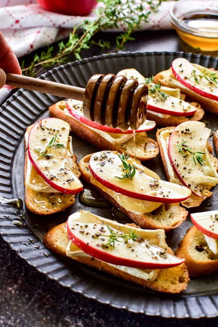 """<p>Melted brie, crisp apples, and a drizzle of honey—this is the perfect pre-holiday bite or fall appetizer. </p><p><strong>Get the recipe at <a href=""""https://www.lemontreedwelling.com/apple-brie-crostini/"""" rel=""""nofollow noopener"""" target=""""_blank"""" data-ylk=""""slk:Lemon Tree Dwelling"""" class=""""link rapid-noclick-resp"""">Lemon Tree Dwelling</a>.</strong></p>"""