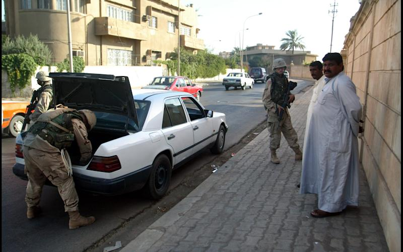 A car is searched at an impromptu US army checkpoint in Baghdad, July 2003 - Credit: Heathcliff O'Malley/-