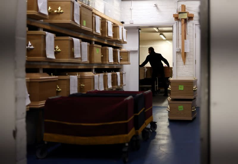 A funeral director moves coffins containing the bodies of deceased people in the mortuary at W. Uden & Sons Family Funeral Directors in Sidcup, amid the coronavirus disease (COVID-19) pandemic, in south east London