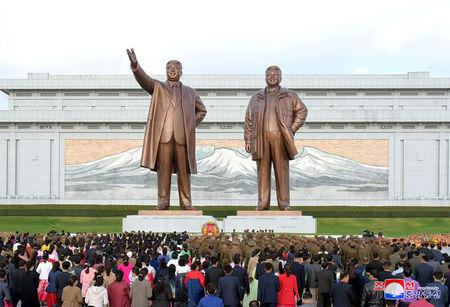FILE PHOTO: People's Army soldiers, workers and students bring flowers to the statues of Kim Il Sung and Kim Jong Il on the 73rd anniversary of the founding of the Korean Workers' Party