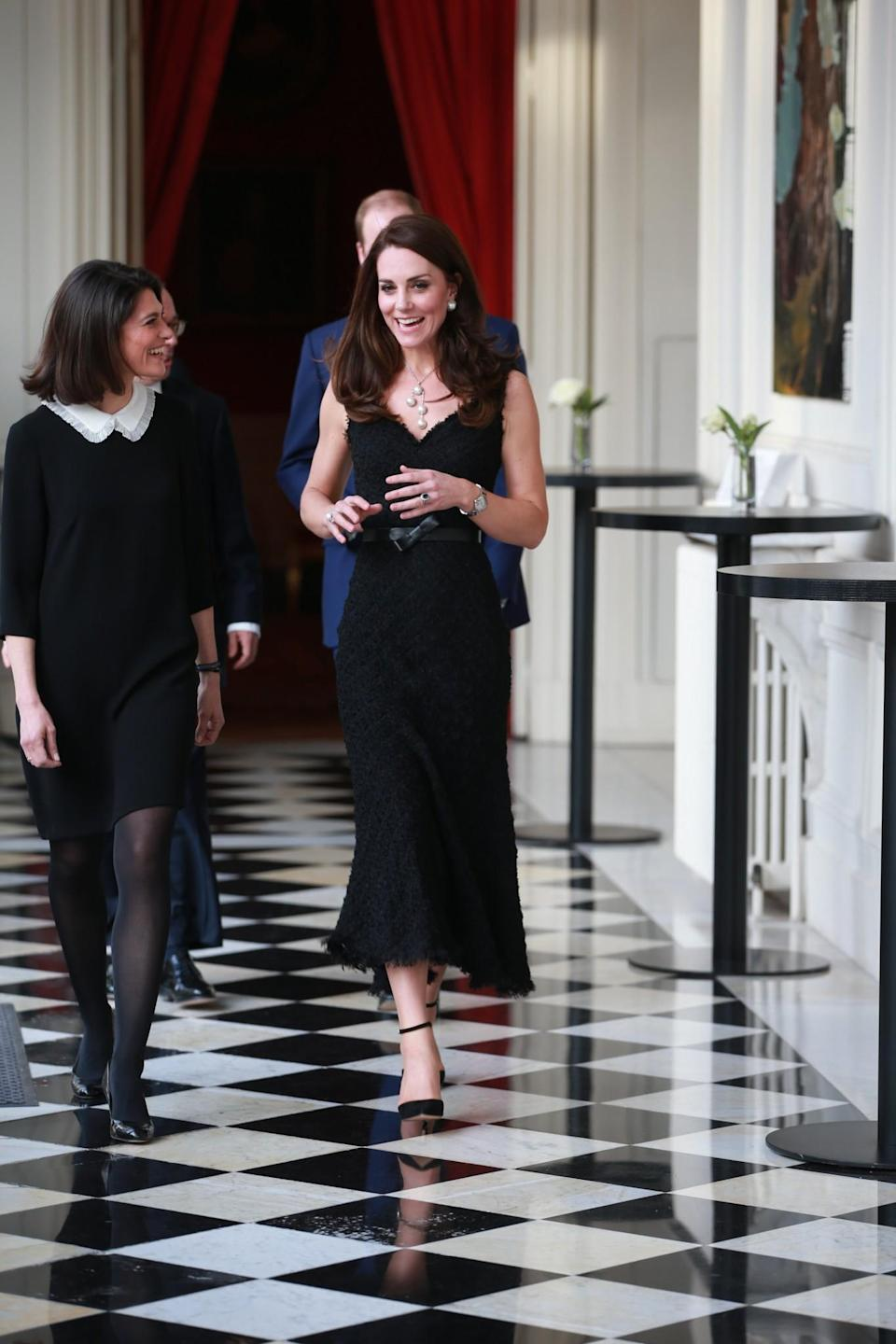 <p>For her arrival in Paris, Kate chose a textured black dress by trusted British label, Alexander McQueen. It was one of the few sleeveless designs the Duchess has donned over the years and appeared to be made from a fringed lace fabric. Kate's jewellery could not be ignored. Huge pearl Balenciaga earrings and a stand-out matching necklace added a nice touch to the elegant look which was finished off with suede Gianvito Rossi heels.<br><i>[Photo: PA]</i> </p>