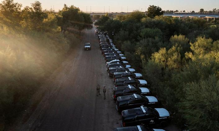State troopers with the Texas department of public safety stand next to a line of law enforcement vehicles facing the US-Mexico border near a makeshift border camp along the International Bridge in Del Rio.