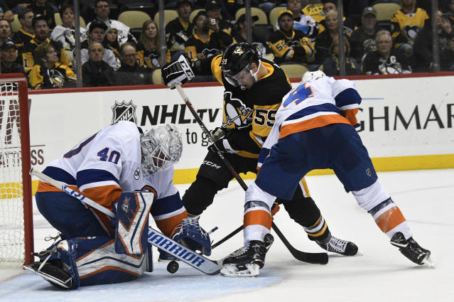 Pittsburgh Penguins left wing Jake Guentzel (59) tries to beat New York Islanders goaltender Robin Lehner (40) and defenseman Thomas Hickey (4) during the second period of an NHL hockey game in Pittsburgh, Tuesday, Oct. 30, 2018. (AP Photo/Don Wright)