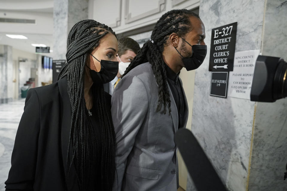 Richard Sherman, right, walks with his wife Ashley, Friday, July 16, 2021, following a King County District Court hearing in Seattle. The NFL football cornerback, who has played with the Seattle Seahawks and the San Francisco 49ers, was arraigned on five criminal charges Friday after he was arrested Wednesday after police said he crashed his car in a construction zone along a busy highway east of Seattle and then tried to break into his in-laws' home in the suburb of Redmond, Wash. (AP Photo/Ted S. Warren)