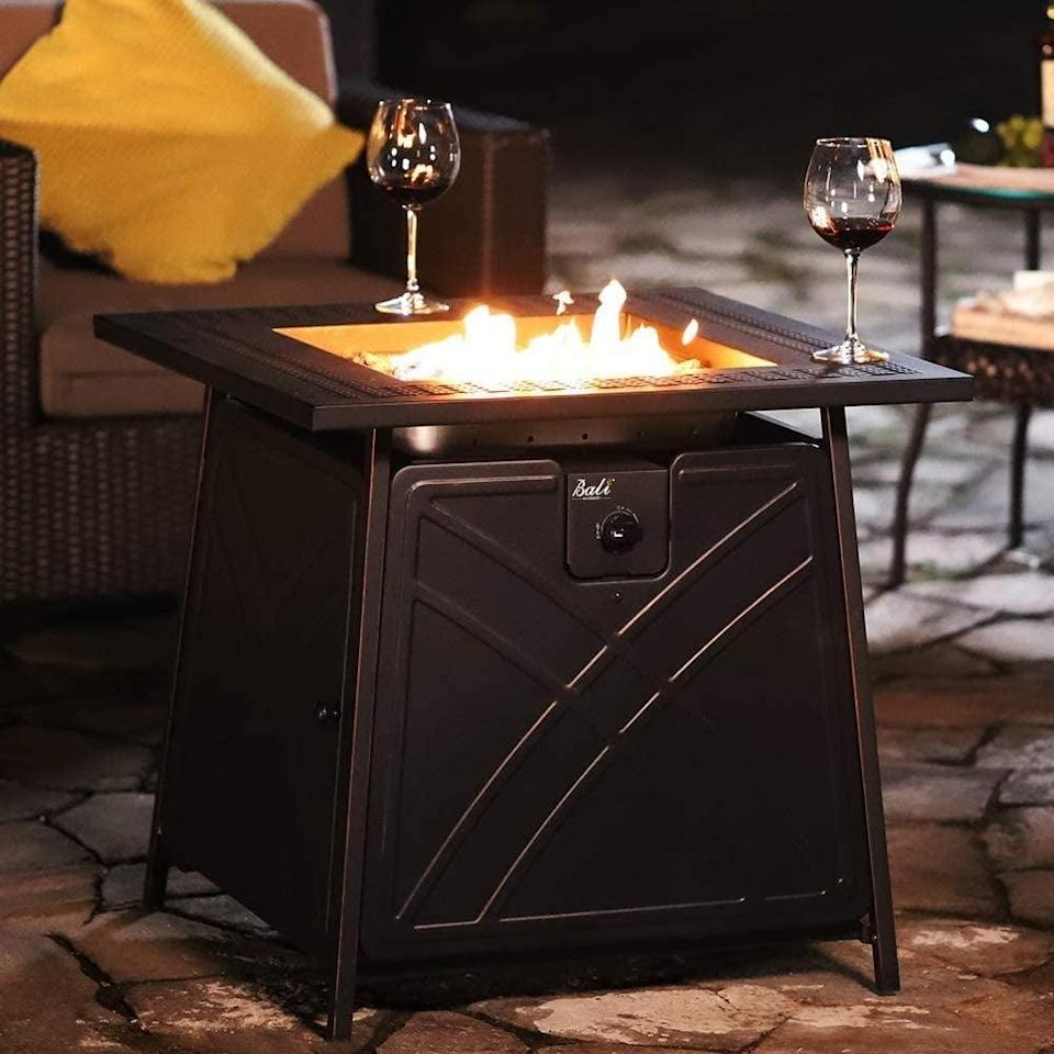 "<p>The <span>BALI OUTDOORS 28"" Fire Pit Table</span> ($210) will give your backyard an instant stylish upgrade. It's a propane based fire pit and table that comes with blue fire glass for a mess-free warm experience. </p>"