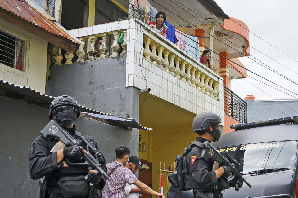 Residents look on as police officers stand guard during a raid on a house that, police believe, is linked to the suicide bombers of Sunday's church attack, in Makassar, South Sulawesi, Indonesia, Monday, March 29, 2021. Two attackers believed to be members of a militant network that pledged allegiance to the Islamic State group blew themselves up outside the packed Roman Catholic cathedral during a Palm Sunday Mass on Indonesia's Sulawesi island, wounding a number of people, police said. (AP Photo/Daeng Mansur)