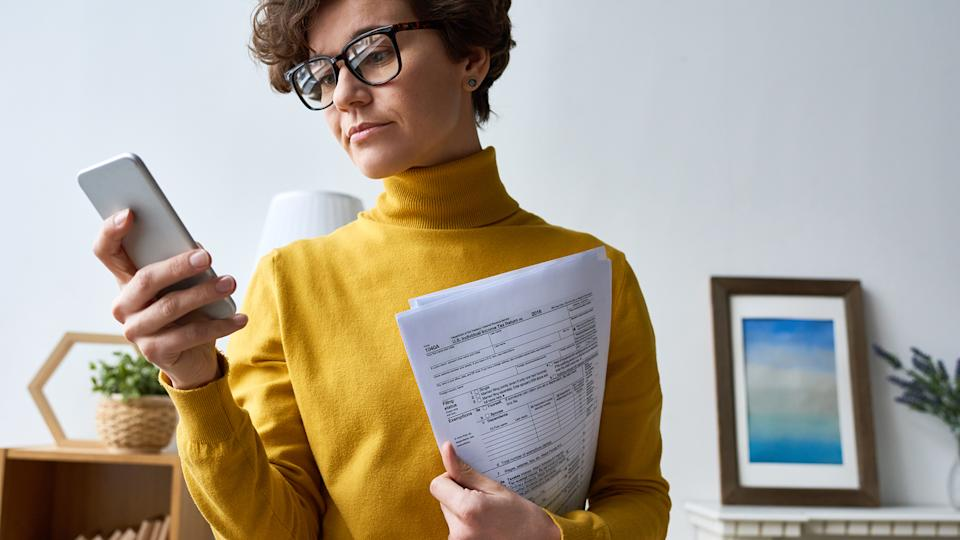 Serious beautiful modern businesswoman holding documents and reading message on smartphone at home.