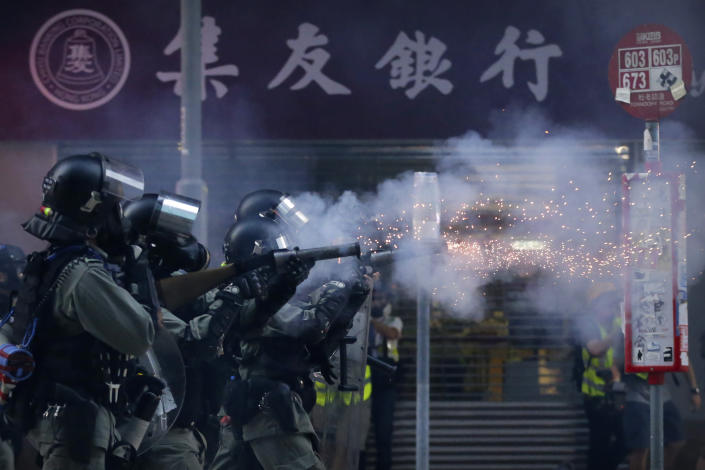 In this Saturday, Nov. 2, 2019, file photo, police in riot gear fire tear gas during a protest in Hong Kong. Hong Kong riot police fired multiple rounds of tear gas and used a water cannon Saturday to break up a rally by thousands of masked protesters demanding meaningful autonomy after Beijing indicated it could tighten its grip on the Chinese territory. (AP Photo/Dita Alangkara, File)