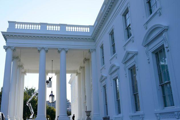 A worker works on the light fixture over the North Portico of the White House in Washington, Friday, Sept. 3, 2021. (AP Photo/Susan Walsh) (Photo: via Associated Press)