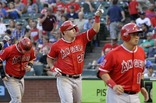 Los Angeles Angels' Mike Trout (27) points to the stands after hitting a three-run home run off of Texas Rangers starting pitcher Colby Lewis that scored Kole Calhoun, left, and Hank Conger, right, in the third inning of a baseball game, Thursday, July 10, 2014, in Arlington, Texas. (AP Photo/Tony Gutierrez)