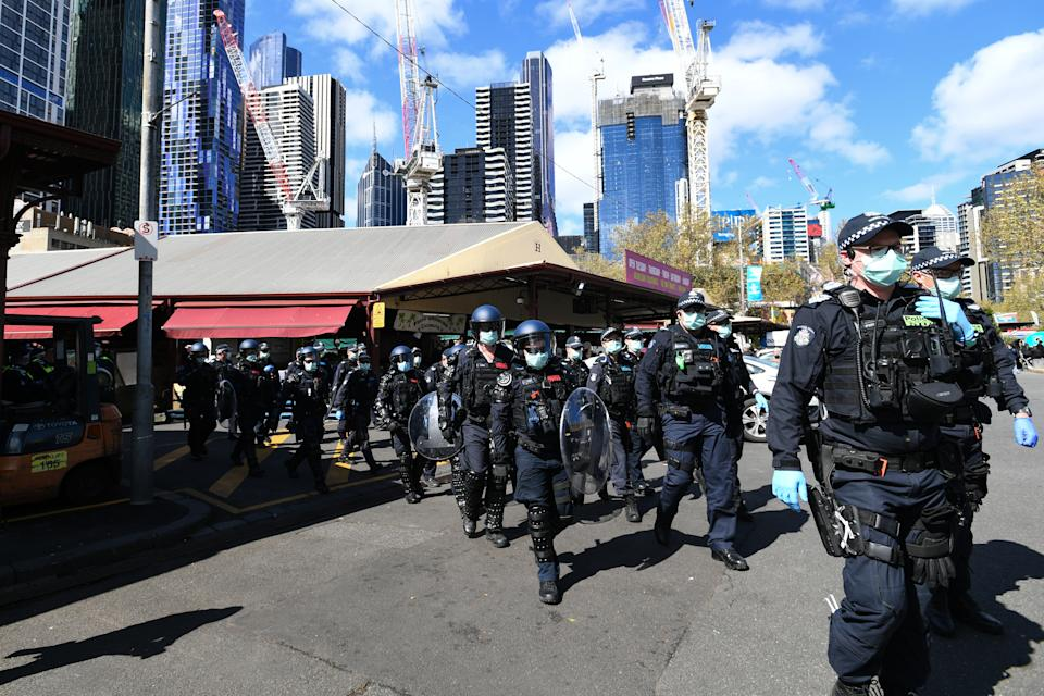 Dozens of police are seen marching through the city.