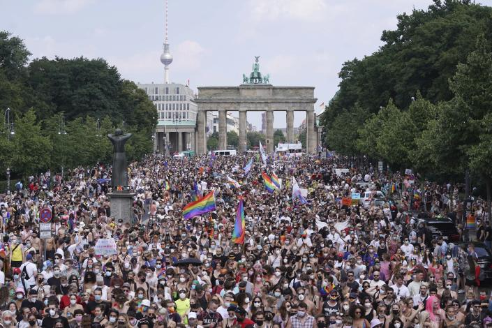 Thousands of people take part in the Christopher Street Day (CSD) parade, with the Brandenburg Gate in the background in Berlin, Germany, Saturday July 24, 2021. (Jorg Carstensen/dpa via AP)