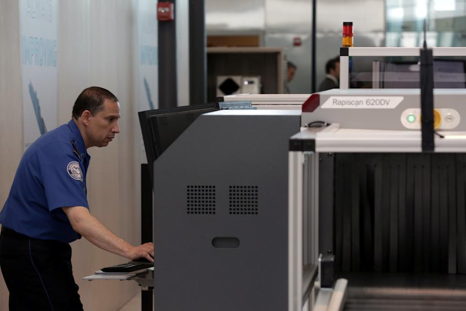 A Transport Security Administration employee scans baggage using new Automated Screening Lane technology at Terminal 4 of JFK airport in New York City, U.S., May 17, 2017. REUTERS/Joe Penney
