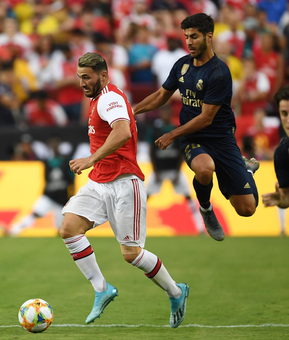 LANDOVER, MARYLAND - JULY 23: Sead Kolasinac of Arsenal breaks past Marco Asensio of Real Madrid during the International Champions Cup match between Real Madrid and Arsenal at FedExField on July 23, 2019 in Landover, Maryland. (Photo by Stuart MacFarlane/Arsenal FC via Getty Images)