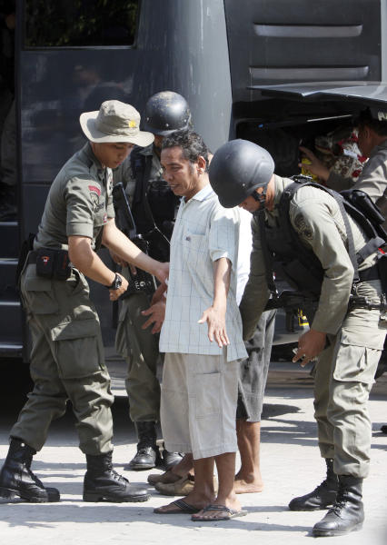 An Indonesian prisoner is frisked by Indonesian special police as he is removed from Kerobokan prison in Denpasar, Indonesia, Friday, Feb. 24, 2012. Indonesia replaced a top warden at the tense, overcrowded prison on Bali island on Friday, after days of rioting forced the evacuation of dozens of foreign inmates, women and children. (AP Photo/Firdia Lisnawati)