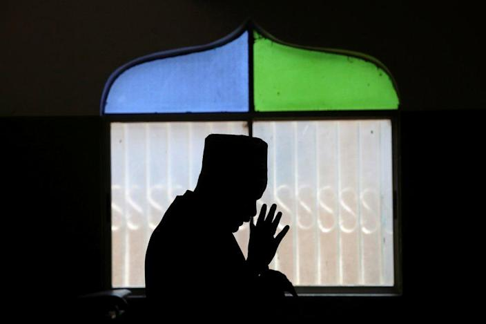 A man prays in a mosque.  His silhouette is seen against the window.