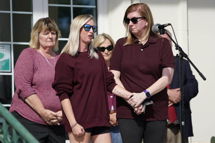 Hollie Skaggs, second from left, holds hands with Sara Wiles as they both speak during a prayer vigil at the Collierville Town Hall, Friday, Sept. 24, 2021, in Collierville, Tenn. Both Skaggs and Wiles were shopping in a Kroger grocery store Thursday when a gunman attacked people, killing one and injuring several, before he was found dead of an apparent self-inflicted gunshot wound. (AP Photo/Mark Humphrey)