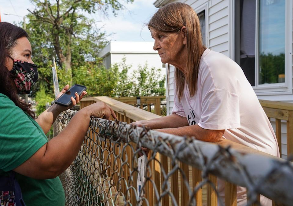 Sharon Bayn (right), 62, of Detroit talks with Congress of Communities parent advocate Cristian Aranda (left) outside Bayn's home on Junction Avenue in the Southwest Detroit neighborhood on Thursday, August 26, 2021. Bayn said she planned to call a number on the handout to figure out how to receive the child tax credit for her 15-year-old grandson that she has custody of.