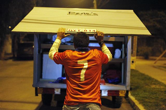 """Chile soccer fan Cristian Uribarri closes the back of the trailer which he built from scratch that he'll pull behind a vehicle during a trip with four friends to Brazil for the World Cup soccer tournament, in Santiago, Chile, as he prepares for the trip late Thursday, June 5, 2014. The shiny contraption they call their """"Lunar Vehicle"""" has air conditioning, a stove, an LCD TV, a Playstation and a queen-sized mattress. Using the mini-home on wheels will save them on lodging and meals. (AP Photo/Luis Hidalgo)"""