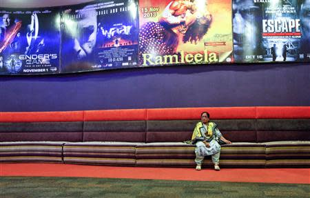 """A poster for the movie """"Waar"""" (2nd L) hangs near a woman sitting a on couch in the lobby of Atrium cinemas in Karachi, ahead of the movie's screening, October 23, 2013. REUTERS/Akhtar Soomro"""
