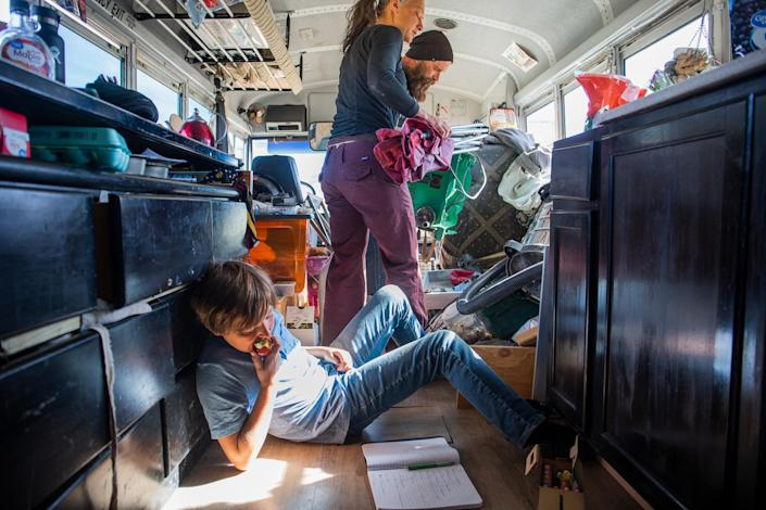 """Max works on chemistry schoolwork on the floor of the bus, while Paula lends her table saw to a neighbor to work on his own bus on Feb. 23.<span class=""""copyright"""">Nina Riggio for TIME</span>"""