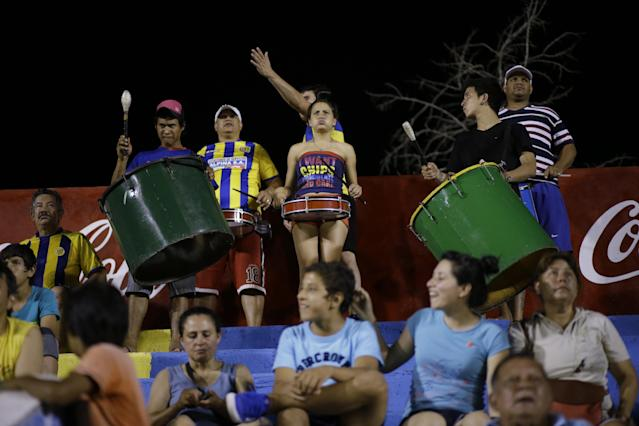 In this Oct. 18, 2014 photo, fans of the Deportivo Capiata soccer team play drums in the stands during a national league match against Cerro Porteno in Capiata, Paraguay. The young team has a tiny fan base, and everything about the club is modest: its dressing room, workout room and stadium amenities. (AP Photo/Jorge Saenz)
