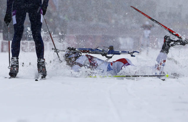 France's Martin Fourcade falls next to Norway's Emil Hegle Svendsen (L) as as they cross the finish line during the men's biathlon 15 km mass start event at the 2014 Sochi Winter Olympics February 18, 2014. Svendsen finished first ahead of Fourcade and Czech Republic's Ondrej Moravec. REUTERS/Carlos Barria (RUSSIA - Tags: OLYMPICS SPORT BIATHLON TPX IMAGES OF THE DAY)