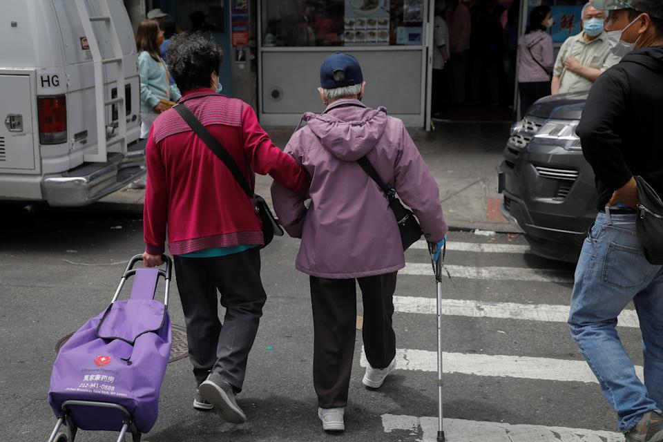 An elderly couple cross Bayard Street near the site of the May 31, 2021 unprovoked attack on an Asian person, a 55 year old woman, in Manhattan's Chinatown district in New York City, U.S. June 2, 2021. REUTERS/Mike Segar