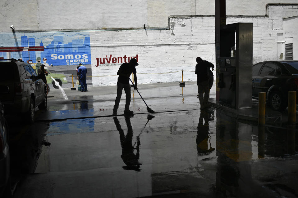A city worker sweeps disinfectant on the ground as a preventive measure amid the spread of the new coronavirus at a state-run gas station in Caracas, Venezuela, Monday, June 29, 2020. (AP Photo/Matias Delacroix)
