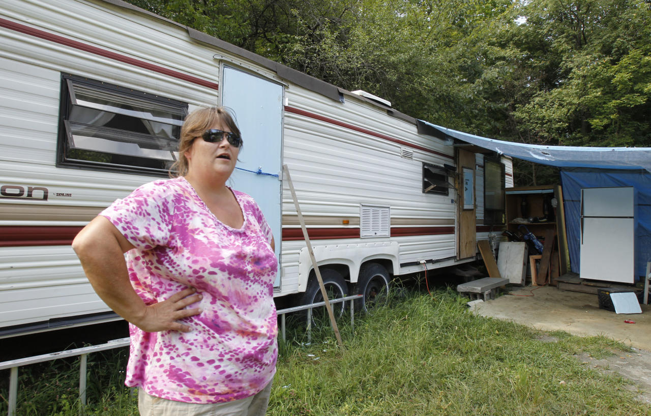 In this Aug. 17, 2012 photo, Janet Lumbra stands outside the recreational trailer where she lives in East Granville, Vt. For some, there will be block parties and parades. For others, a moment of silence. Or it might be just another day of struggling to clean up the mess. But if there's one unifying event to mark the first anniversary of Irene, it'll probably be the 30 seconds of ringing of bells in churches and town halls across Vermont that Gov. Peter Shumlin has requested for 7 p.m. Tuesday, Aug. 28, 2012, a year to the day after the storm changed Vermont forever.