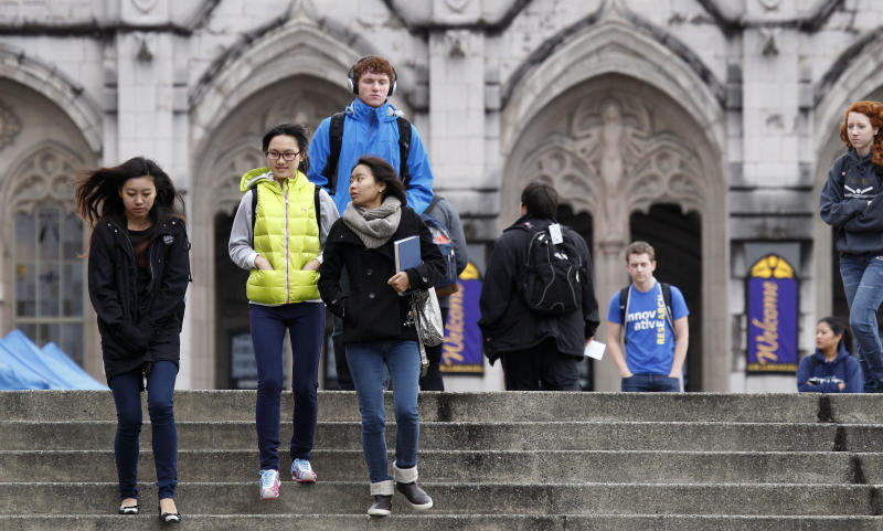 University of Washington students walk on the campus between classes Tuesday, Oct. 23, 2012, in Seattle. The university has about a thousand more international students on the campus this fall, but university officials say that doesn't mean they have cut back on the number of in-state students at the state's most selective public university. (AP Photo/Elaine Thompson)