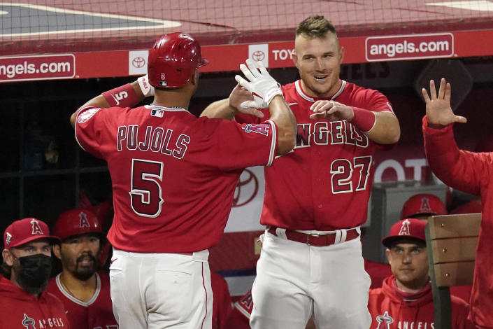Los Angeles Angels' Albert Pujols, left, is congratulate by Mike Trout after hitting a solo home run during the seventh inning of a baseball game against the Texas Rangers Tuesday, April 20, 2021, in Anaheim, Calif. (AP Photo/Mark J. Terrill)