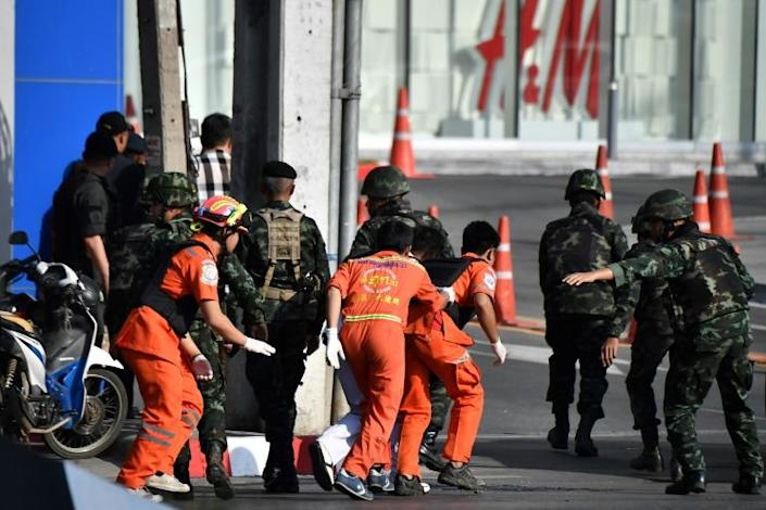 Thai medical personnel (in orange) prepare to enter the Terminal 21 mall to help the wounded inside, while the gunman was still on the loose (AFP Photo/Lillian SUWANRUMPHA)