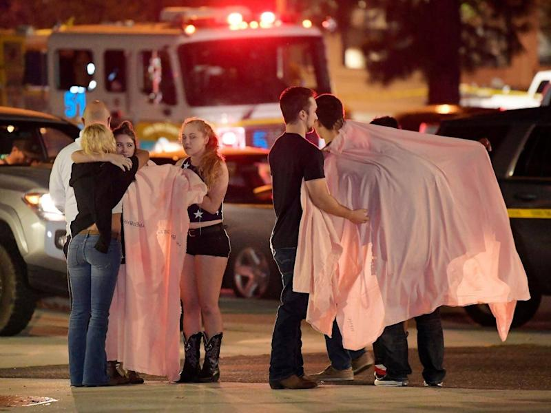 People comfort each other as they stand near the scene 8 November, 2018, in Thousand Oaks, California, where a gunman opened fire inside a country dance bar crowded with hundreds of people on
