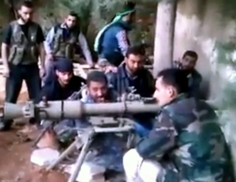 In this image taken from video obtained from the Ugarit News, which has been authenticated based on its contents and other AP reporting, Colonel Abu al-Furat, commander of the battle of the trenches revolutionaries, third left, speaks in Aleppo, Syria, on Monday, Nov. 26, 2012. (AP Photo/Ugarit News via AP video)