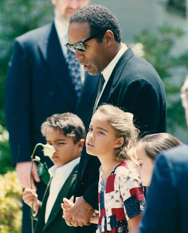 <p>After days of seclusion, O.J. Simpson attends the funeral of his ex-wife on June 16–joining their young kids, Sydney, 8, and Justin, 5, who were asleep at the house on Bundy Drive when their mother was murdered. (Photo: Kevin Winter/Getty Images) </p>