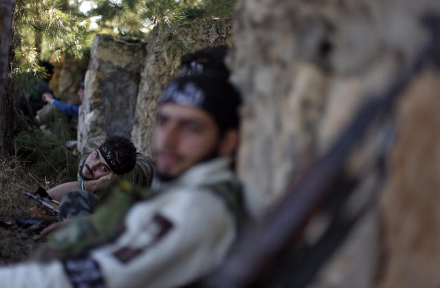 FILE - In this Thursday, Nov. 15, 2012 file photo, Syrian rebels rest during clashes with Syrian troops on Aleppo. Through mid-2012, rebel power grew and Assad's army ramped up its response. Relentless government shelling leveled neighborhoods and killed hundreds. Regular reports emerged of mass killings by the regime or thugs loyal to it, pushing more Syrians toward armed struggle. The government, which considers the opposition terrorist gangs backed by foreign powers, denied any role, and does not respond to requests for comment on its military. The rebels, too, were accused of atrocities. (AP Photo/ Khalil Hamra, File)