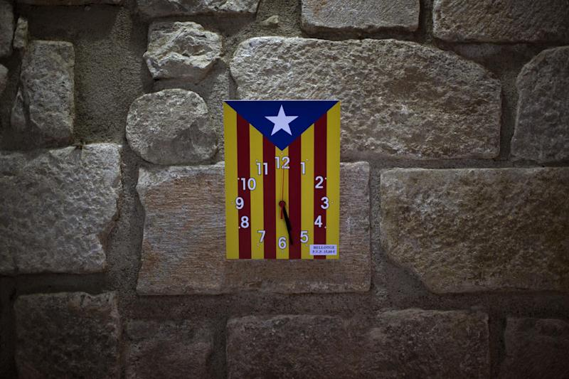 """In this photo taken on Tuesday, Nov. 19, 2012, a clock bearing the """"estelada"""" flag that symbolizes Catalonia's independence is displayed for sale in a book shop in Girona, Spain. Catalonia holds elections on Sunday that will be seen as a test of the regional government's plans to hold a referendum on independence, and one of the key issues emerging is the theoretical place of a free Catalonia in Europe. (AP Photo/Emilio Morenatti)"""
