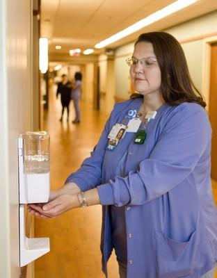 Elmhurst Hospital's Lisa Schmidt, RN, uses one of the soap/sanitizer dispensers that is part of Edward-Elmhurst Heath's SwipeSense Hand Hygiene system. SwipeSense captures information when users enter/exit a patient room and when they clean their hands, only recording hygiene opportunities and events associated with patient room visits.